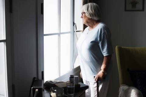 Eenzame oudere vrouw kijkt uit venster