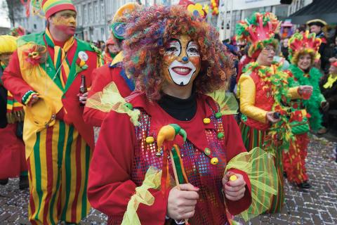 Vrouw verkleed als clown tijdens carnavalstoet