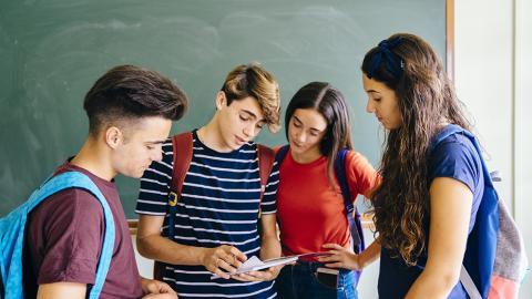 groepje leerlingen discussiëren voor schoolbord
