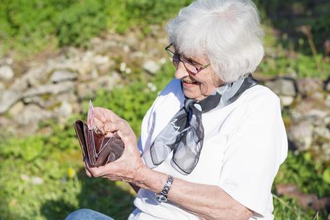 gepensioneerde vrouw kijkt in portefeuille