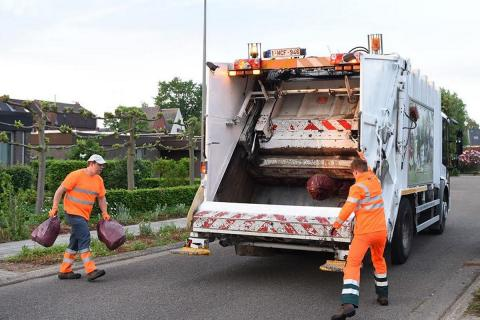 man gooien vuilniszakken in ophaalwagen