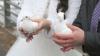 bruidspaar met koppel witte duiven in handen